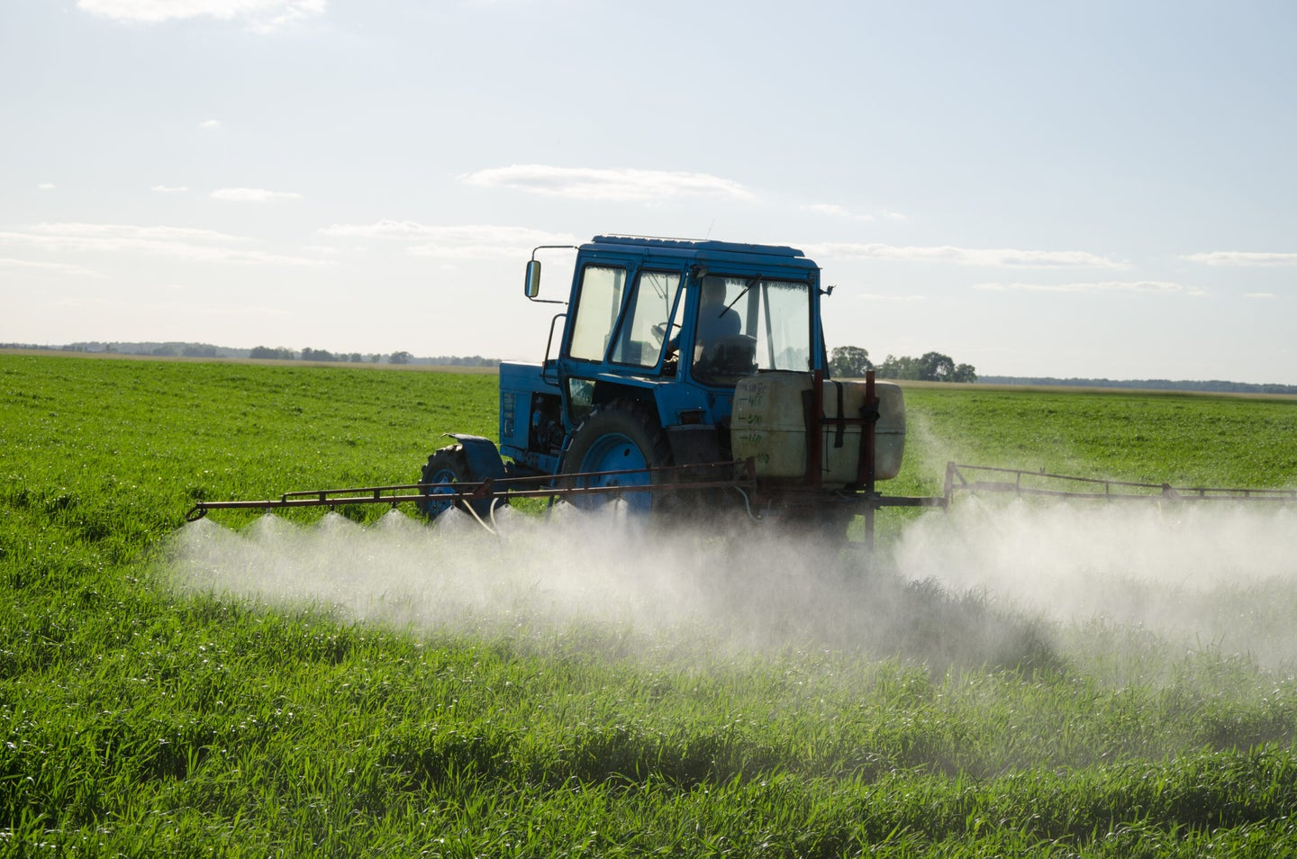 tractor spraying insecticide over field