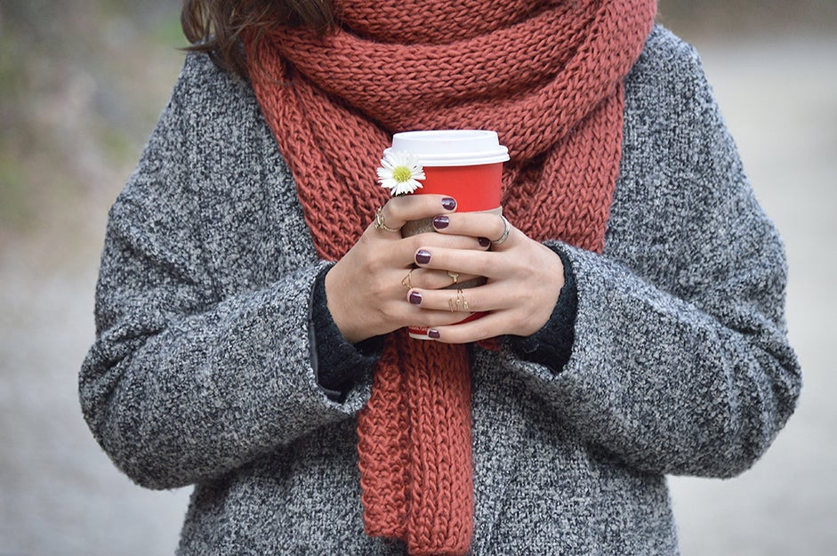 woman with a scarf around neck and coffee in hands