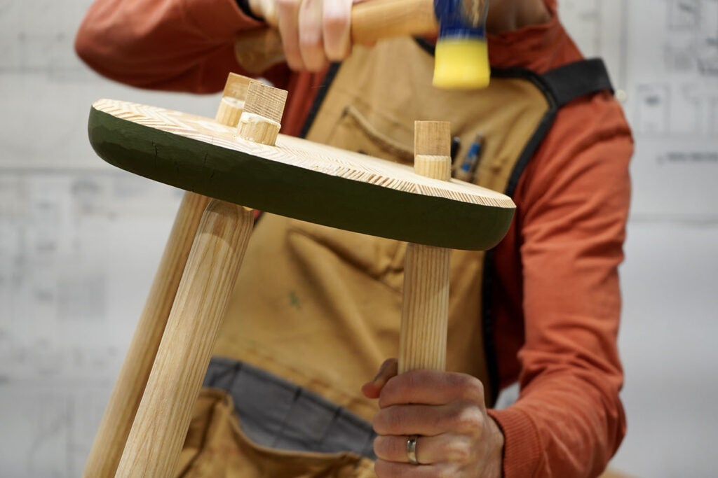 a person using a mallet to drive wooden wedges into a slot in the tenon of the legs of a wooden three-legged stool