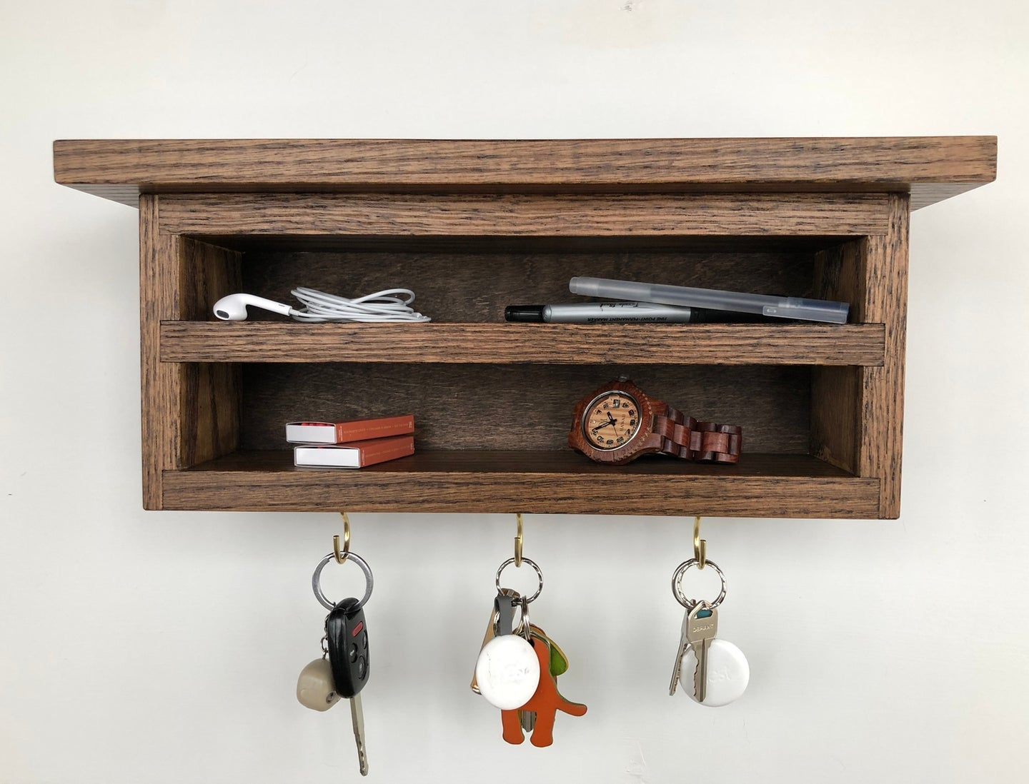 a small oak shelf key organizer cabinet hung with a French cleat so it appears to float on the wall