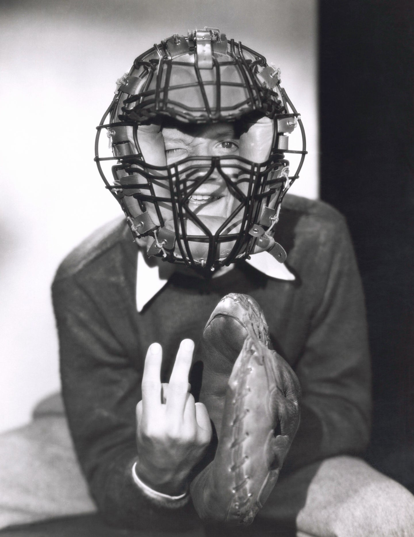 An old-school catcher throwing up a pitch sign