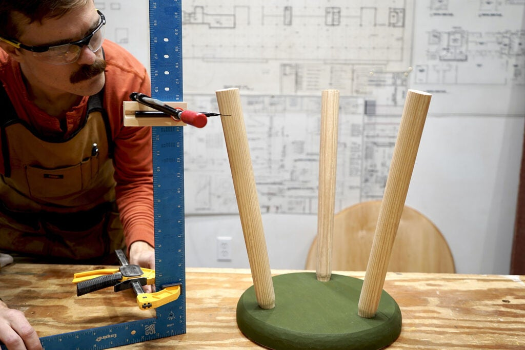 a person using a carpenter's square, a pencil, and a smaller square to ensure they draw level lines on the legs of a wooden three-legged stool