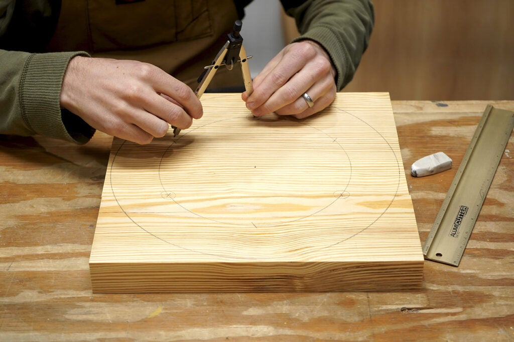 a person using a compass and a pencil to draw circles on pine wood to make the seat of a three-legged stool