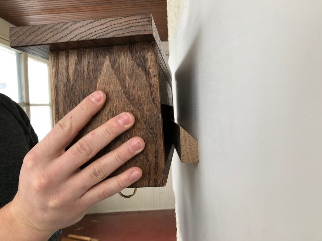 an oak key cabinet shelf that hangs with a French cleat on the wall