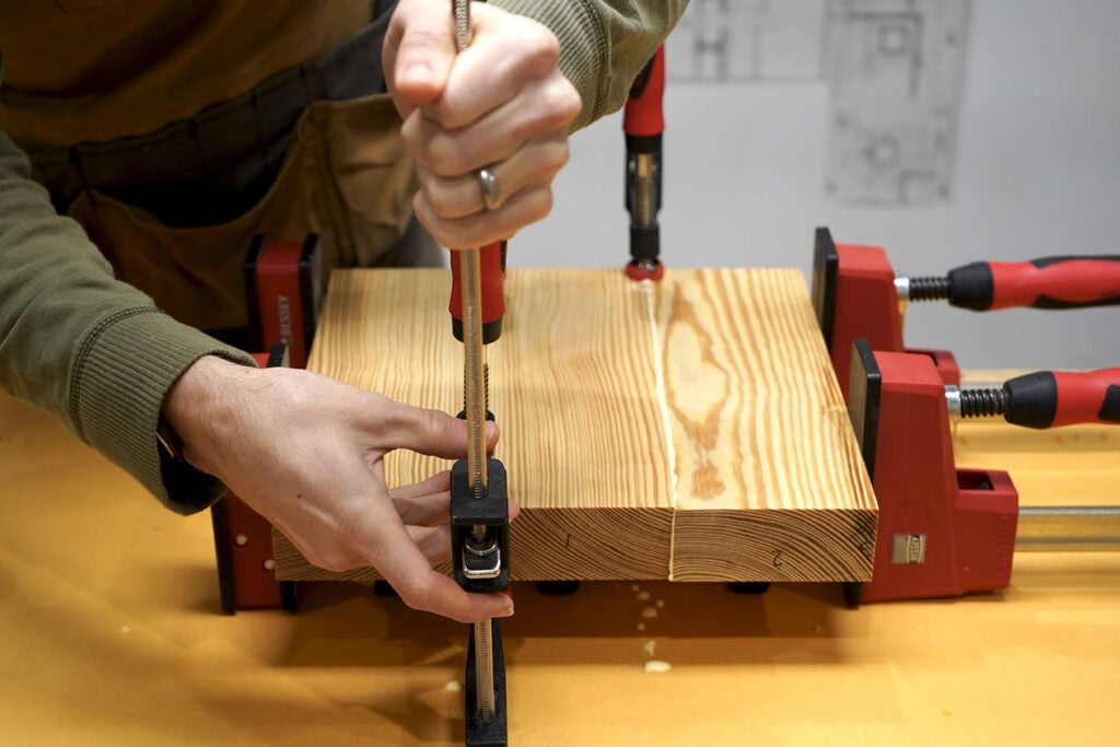a person clamping pine wood together with glue to form the seat of a three-legged stool