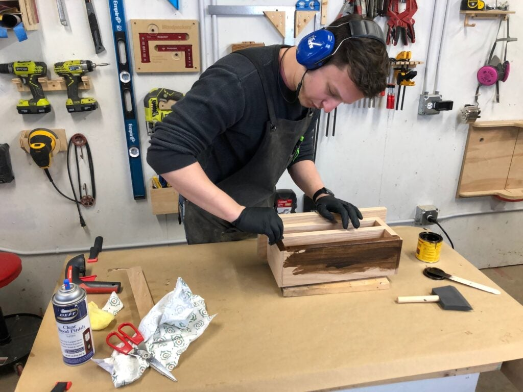 a person applying stain to a key cabinet shelf organizer