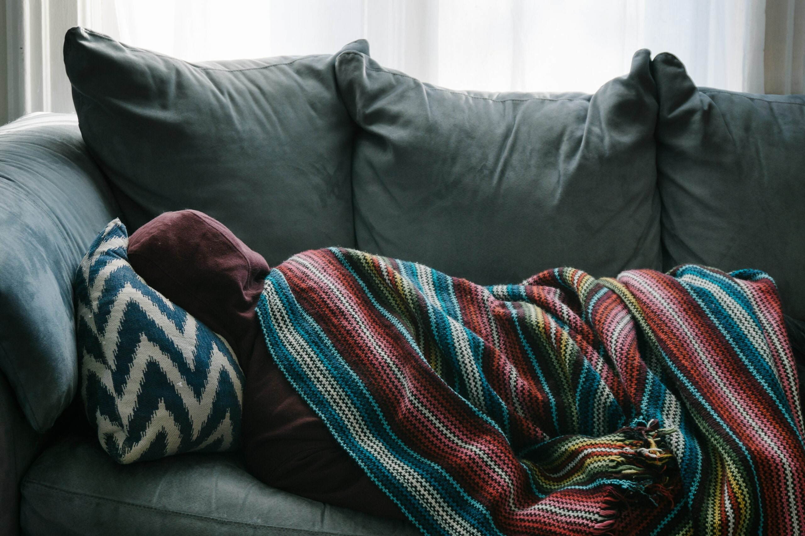 person lying on couch with blanket over them