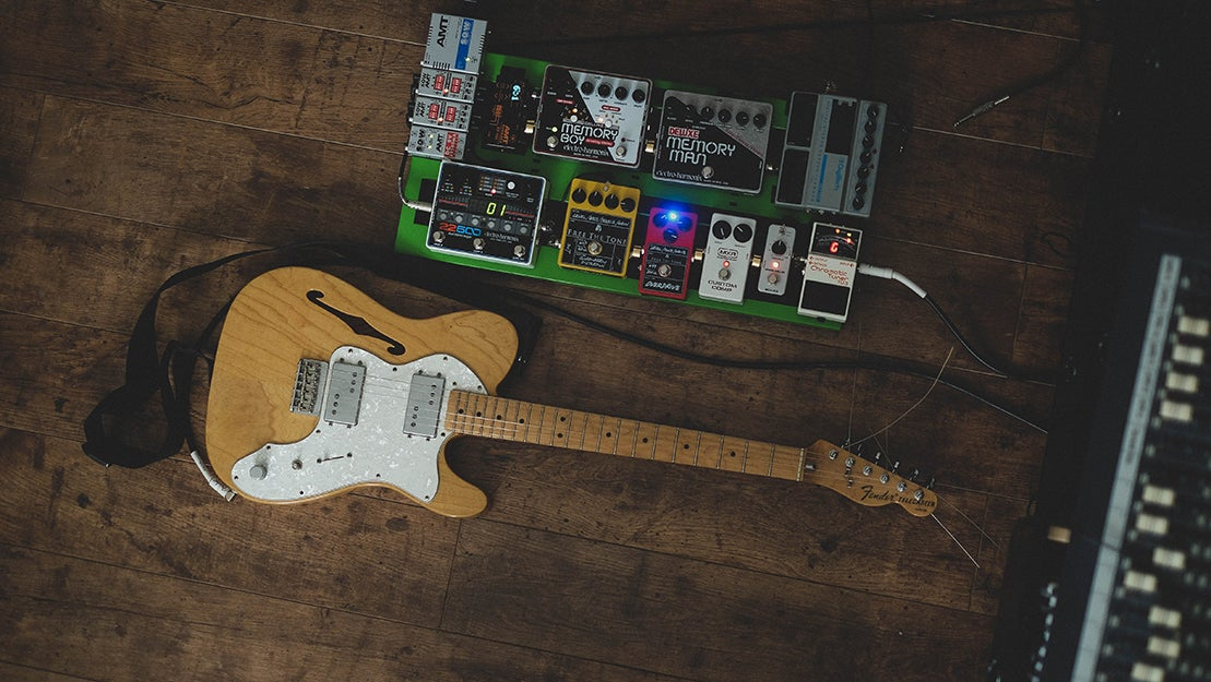 guitar and pedalboard on the floor