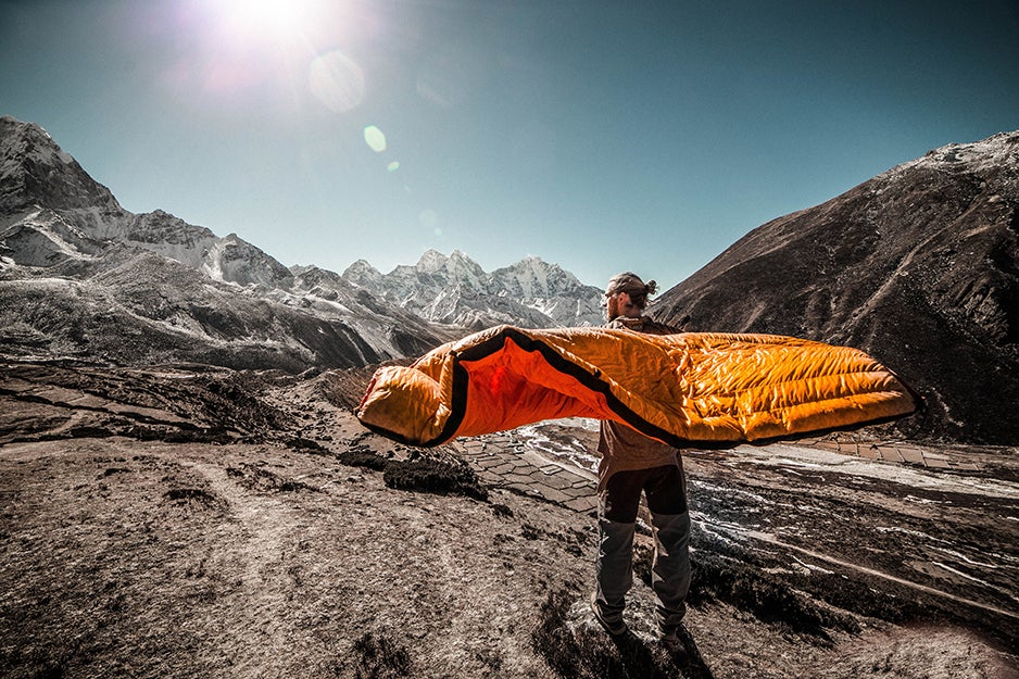 person with a sleeping bag on a mountain