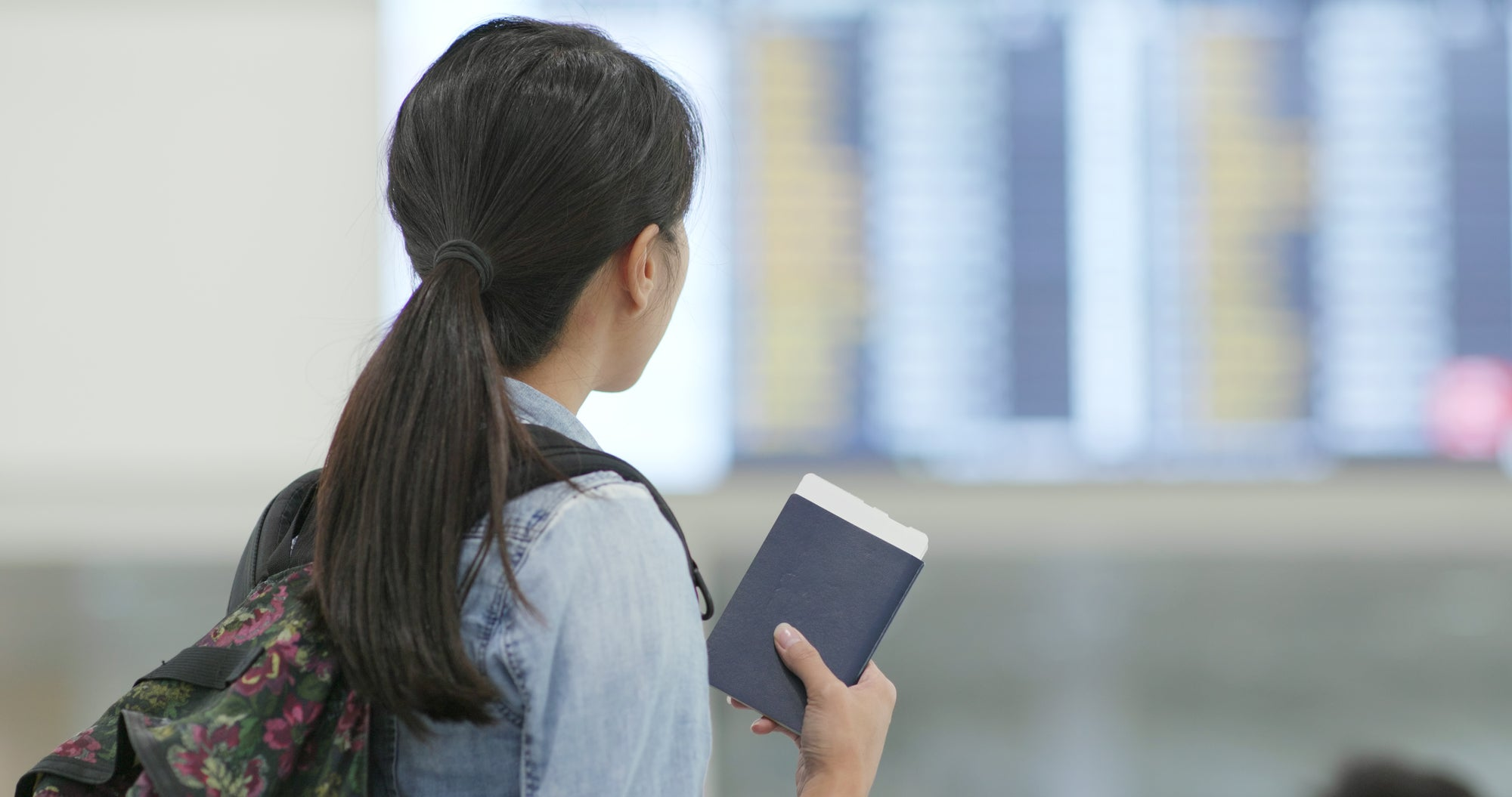 A young asian woman stands in an airport holding a passport