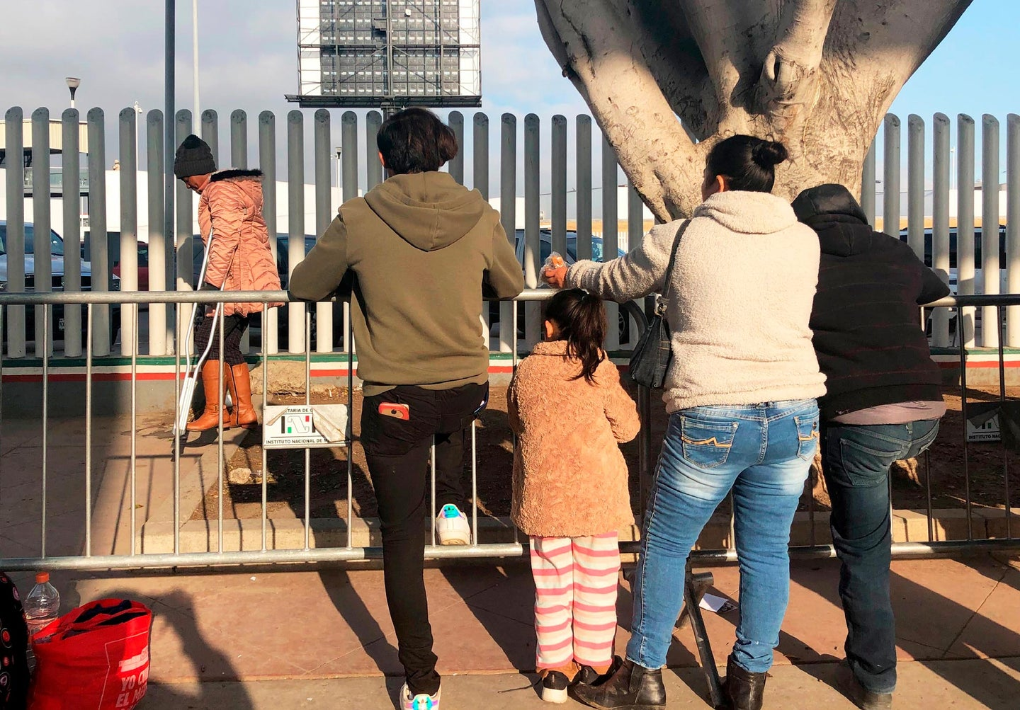 people leaning on metal fence