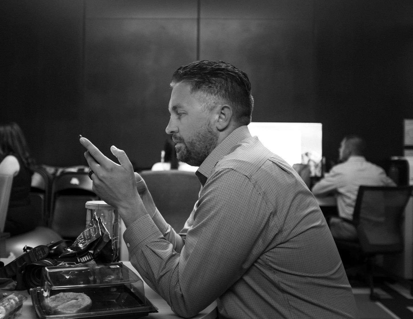 a man sitting at a desk looking at a phone