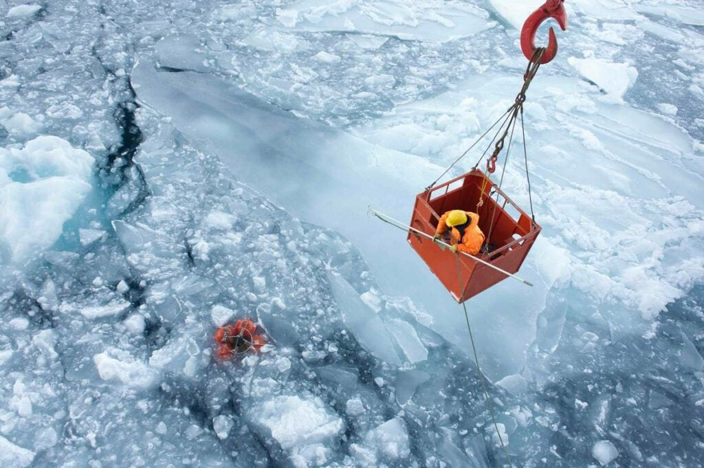 person in crane basket with rope attached to measuring instruments in icy water