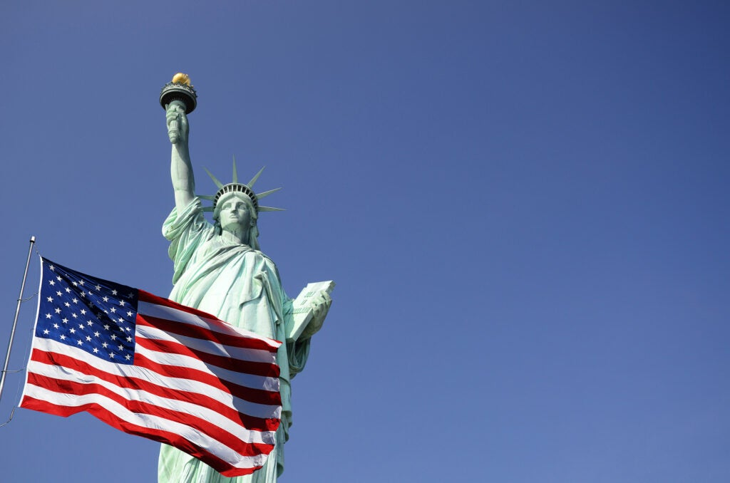 The Statue of Liberty with an American flag flying in front