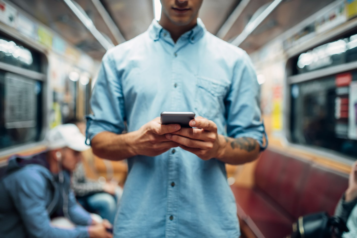 a man holds a phone in his hands on the subway