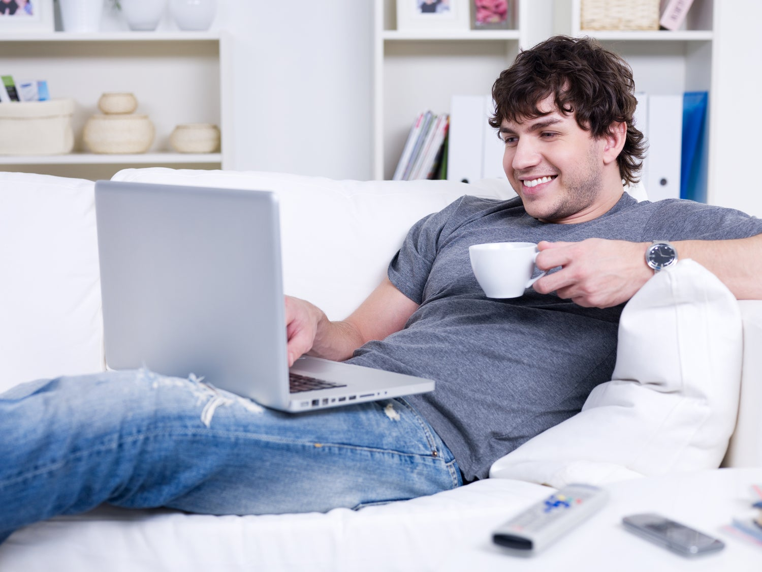 a man on his white couch with a cup of tea or coffee, smiling while using his laptop