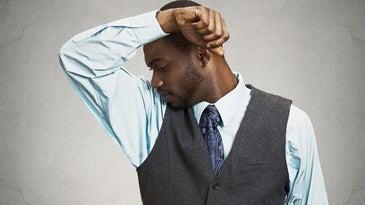 man sniffing his armpit