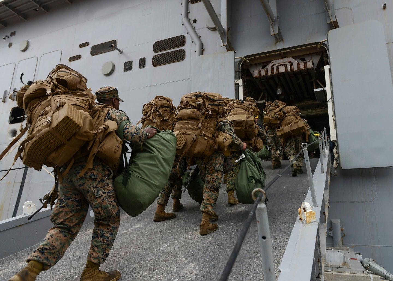 Marines board the amphibious assault ship USS Iwo Jima