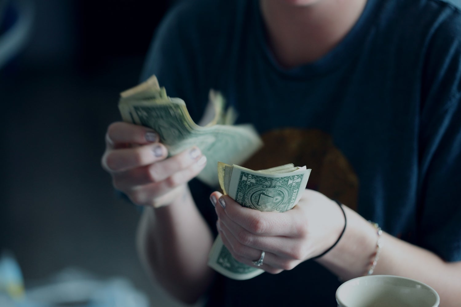 a person counting money in $1 U.S. bills