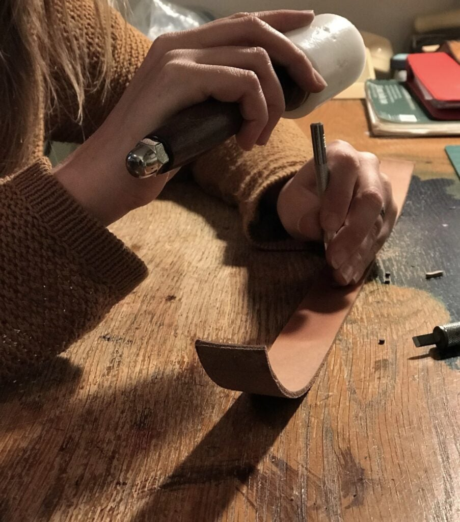 a leatherworker using a maul and a metal stamping tool on a piece of leather