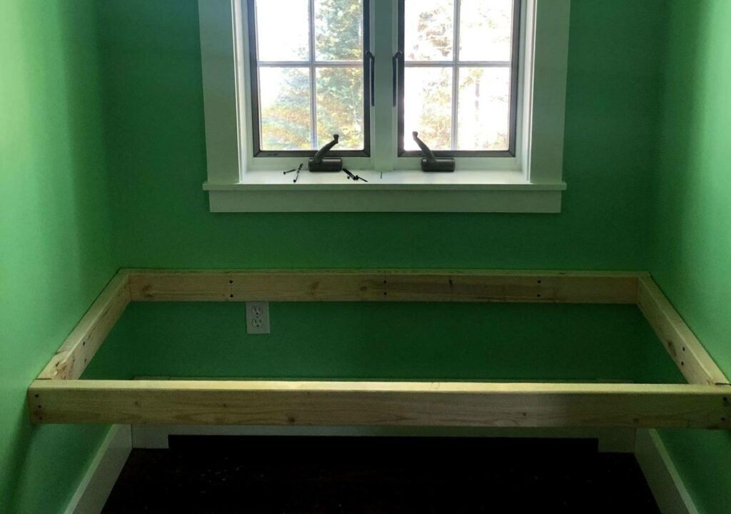 a window seat frame made out of two-by-fours in a dormer window