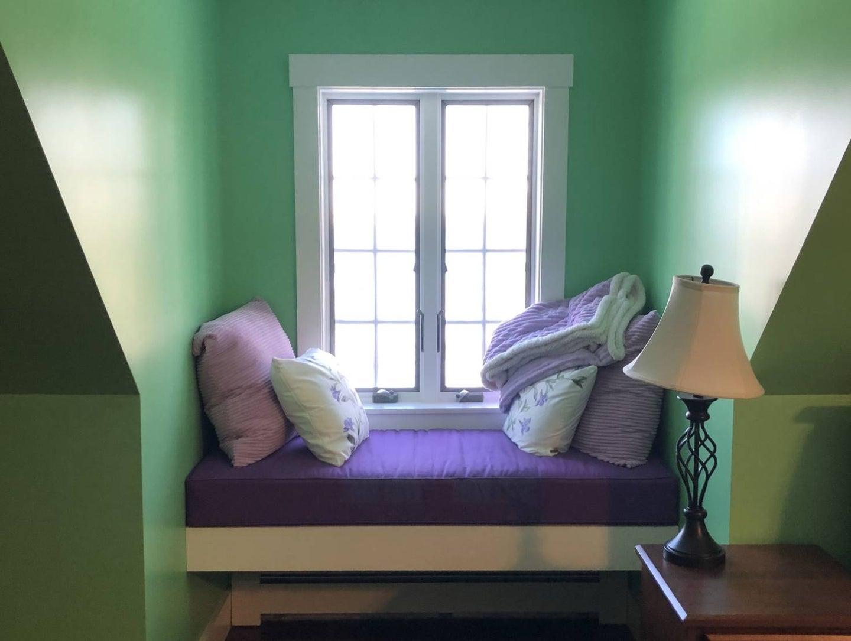 a cushioned window seat in a bedroom dormer window