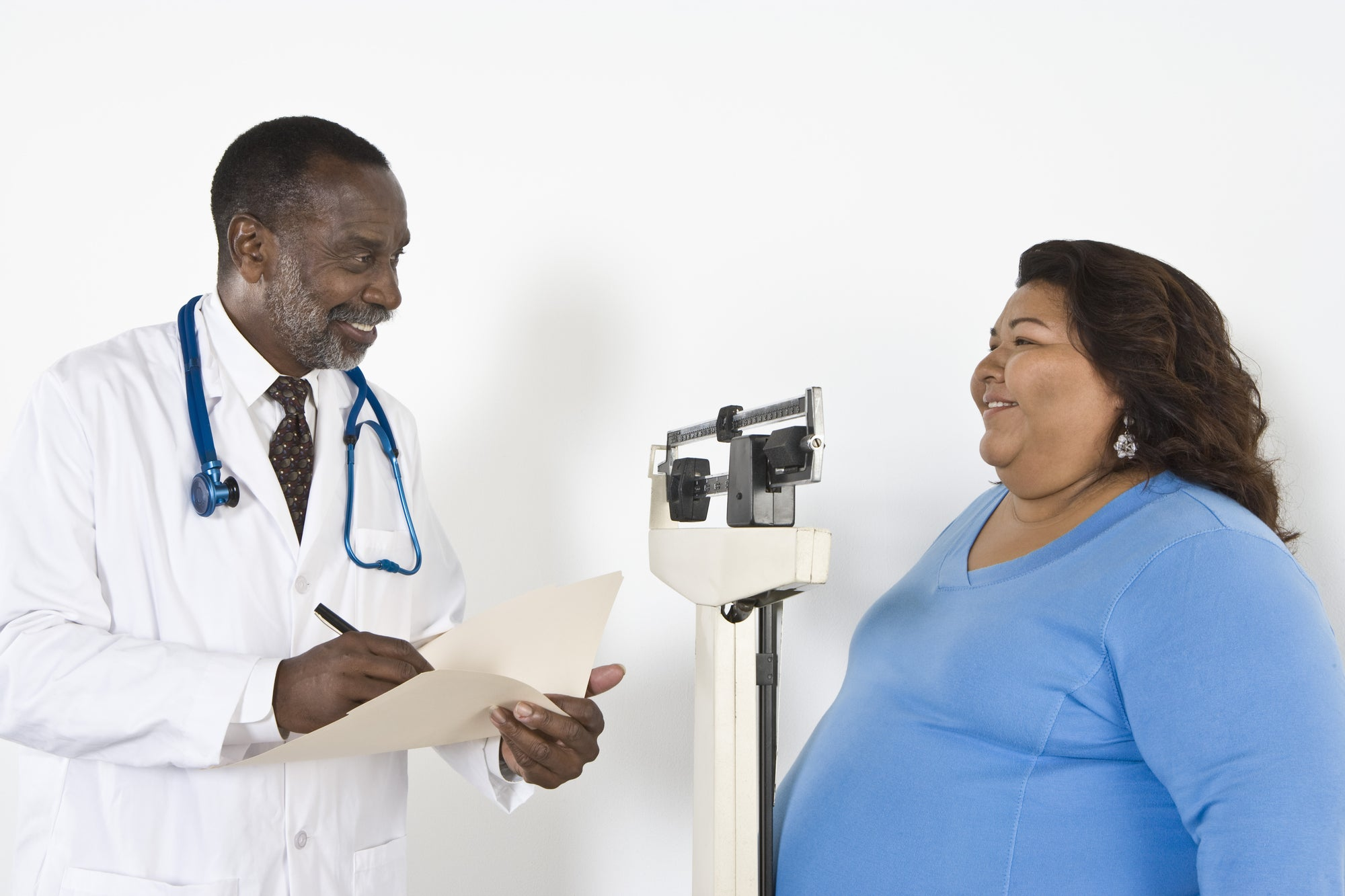 a doctor smiles at a patient while reading her weight off a scale