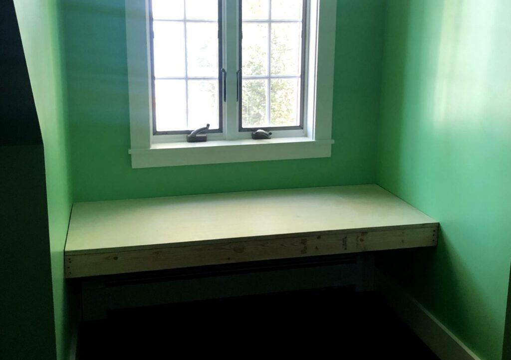 a window seat base made out of two-by-fours and topped with plywood, in a dormer window