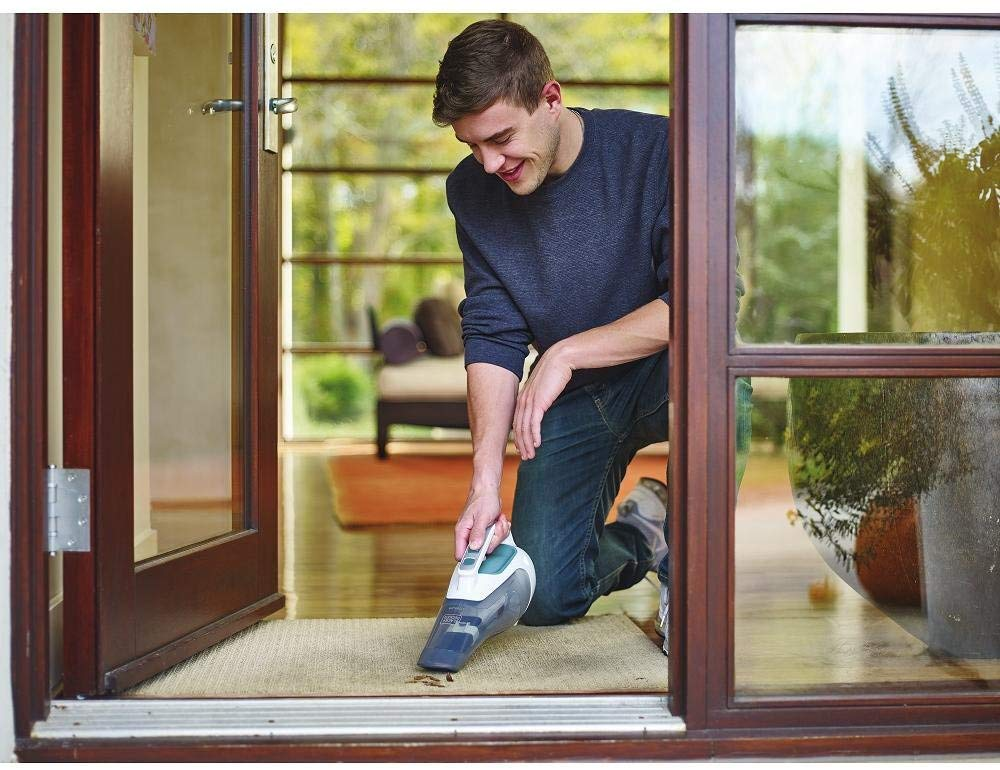 person cleaning rug near door with dustbuster