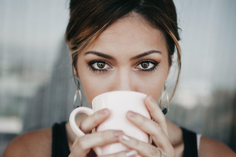 A brown-eyed individual holding a mug