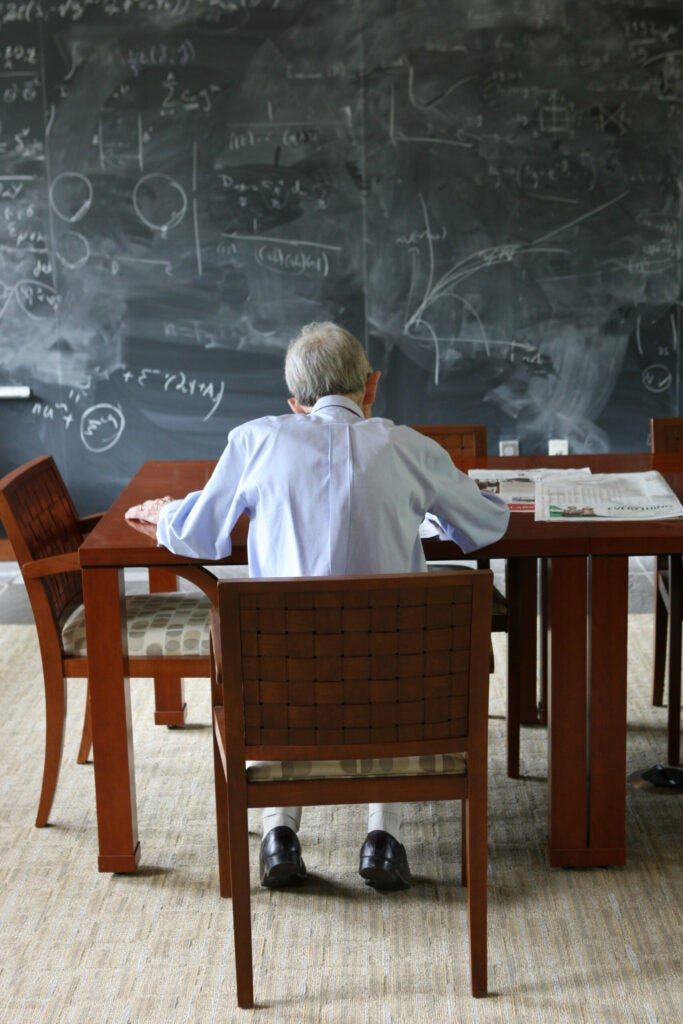 A man working at a table in front of a blackboard covered in equations.