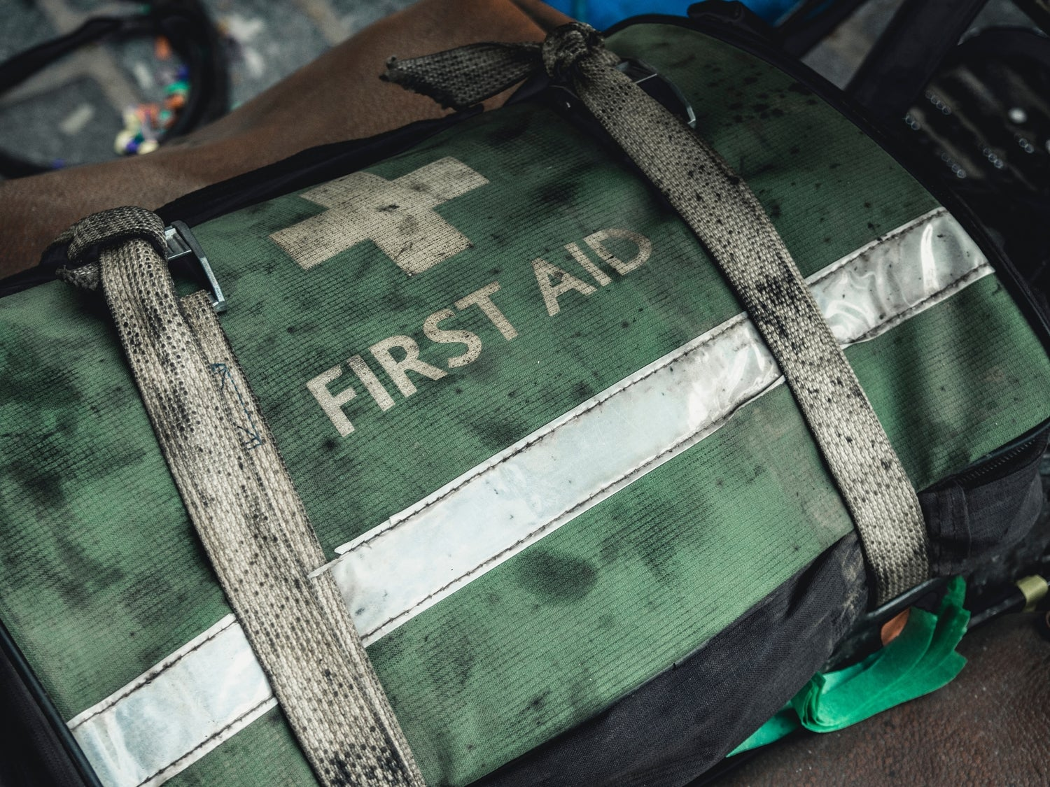 a dirty green and white first aid bag