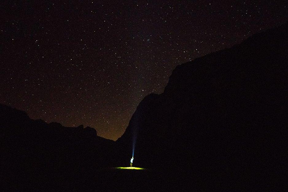 person with flashlight in dark