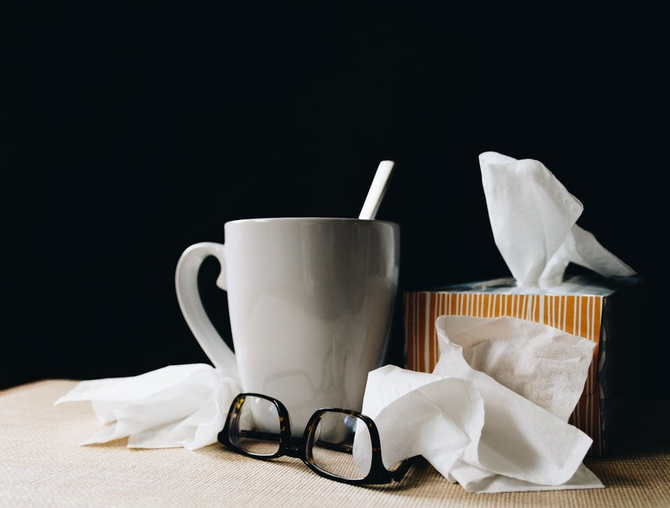 a mug next to a pile of tissues
