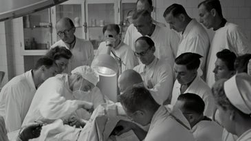 doctors gathered around patient in 1940s