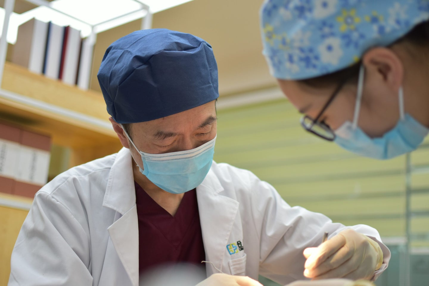 A Chinese doctor standing over a patient