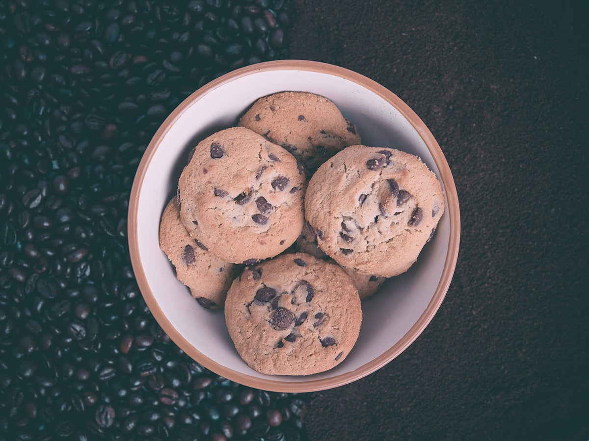 a bowl of chocolate chip cookies on a bed of whole coffee beans and ground coffee