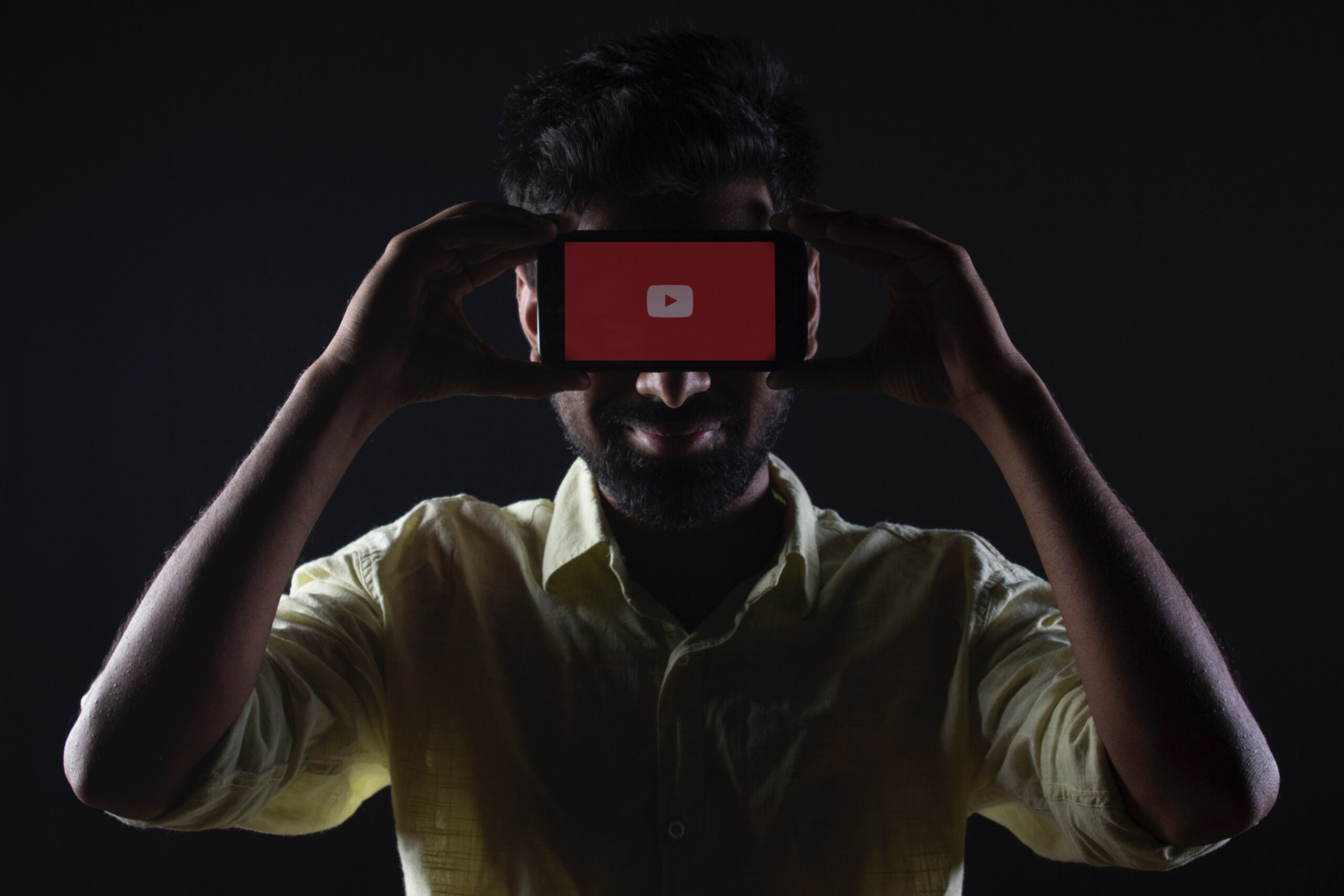 A man holds a smartphone with the YouTube app.