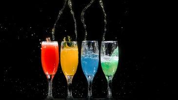 four champagne glasses full of colorful liquid