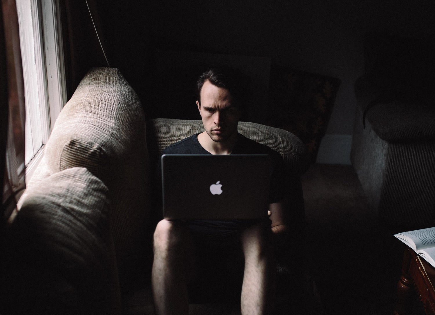 a man sitting solemnly on a couch in the dark with his Apple Mac laptop