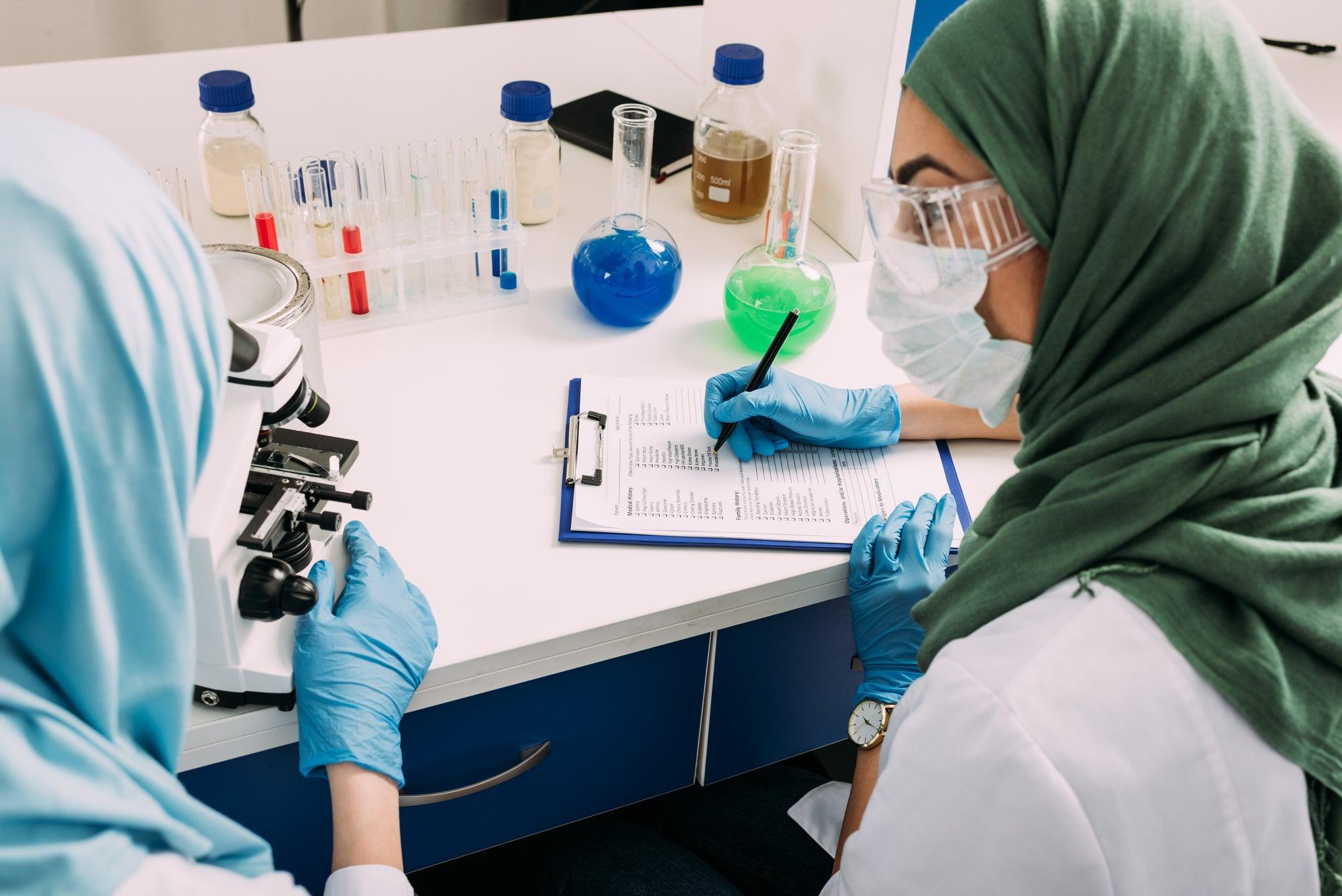 Masked researchers handling samples