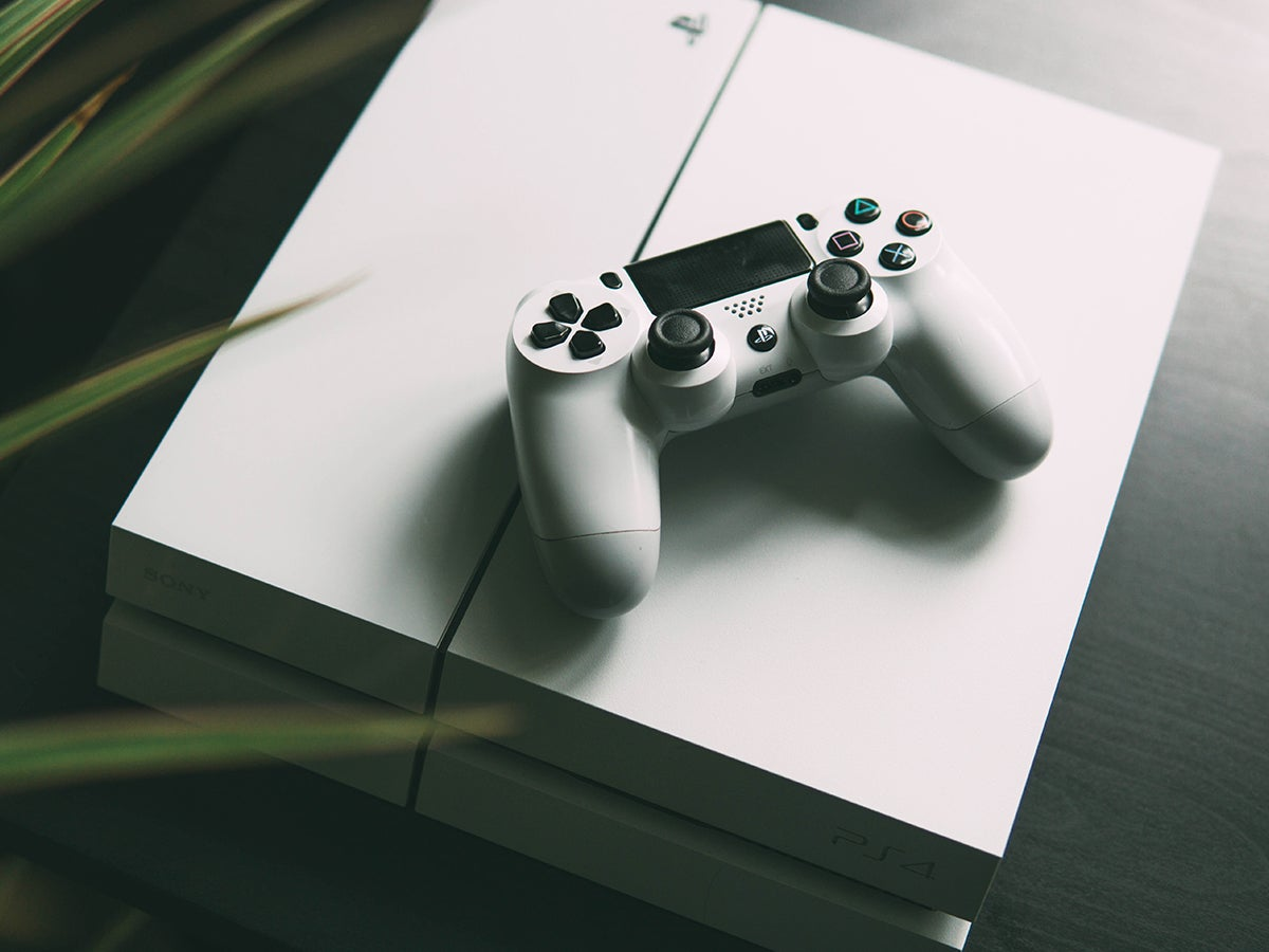 a photo of a white PlayStation 4 (PS4), with a controller