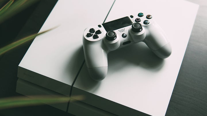 A white PlayStation 4 with a white controller on top of it, ready to help you add more PS4 storage.