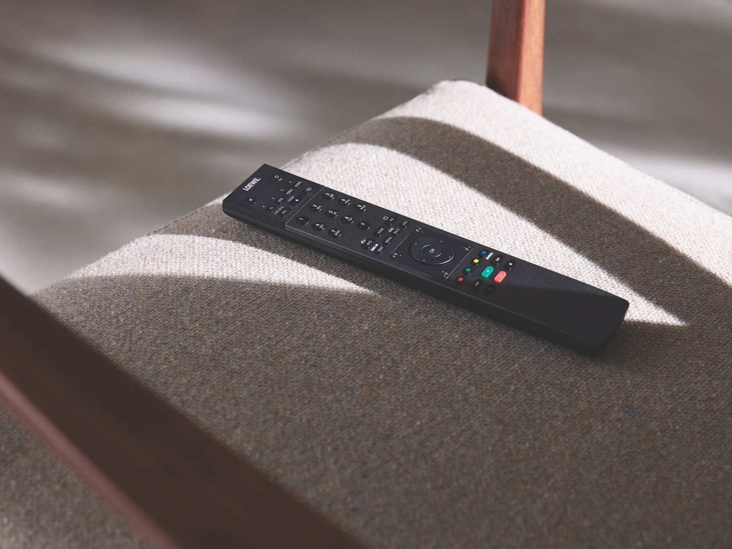 a black TV remote on a gray chair
