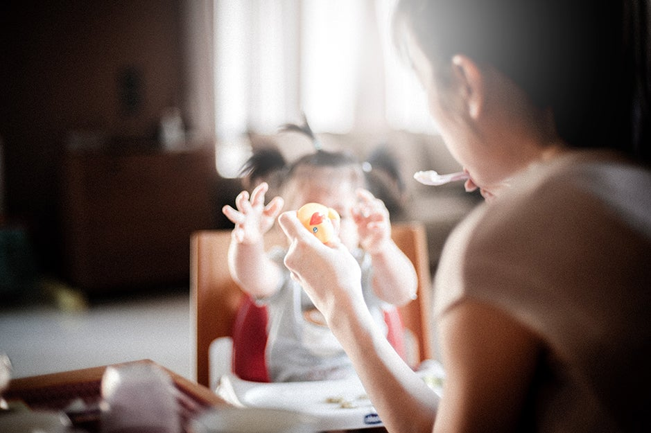 mother feeding child in high chair