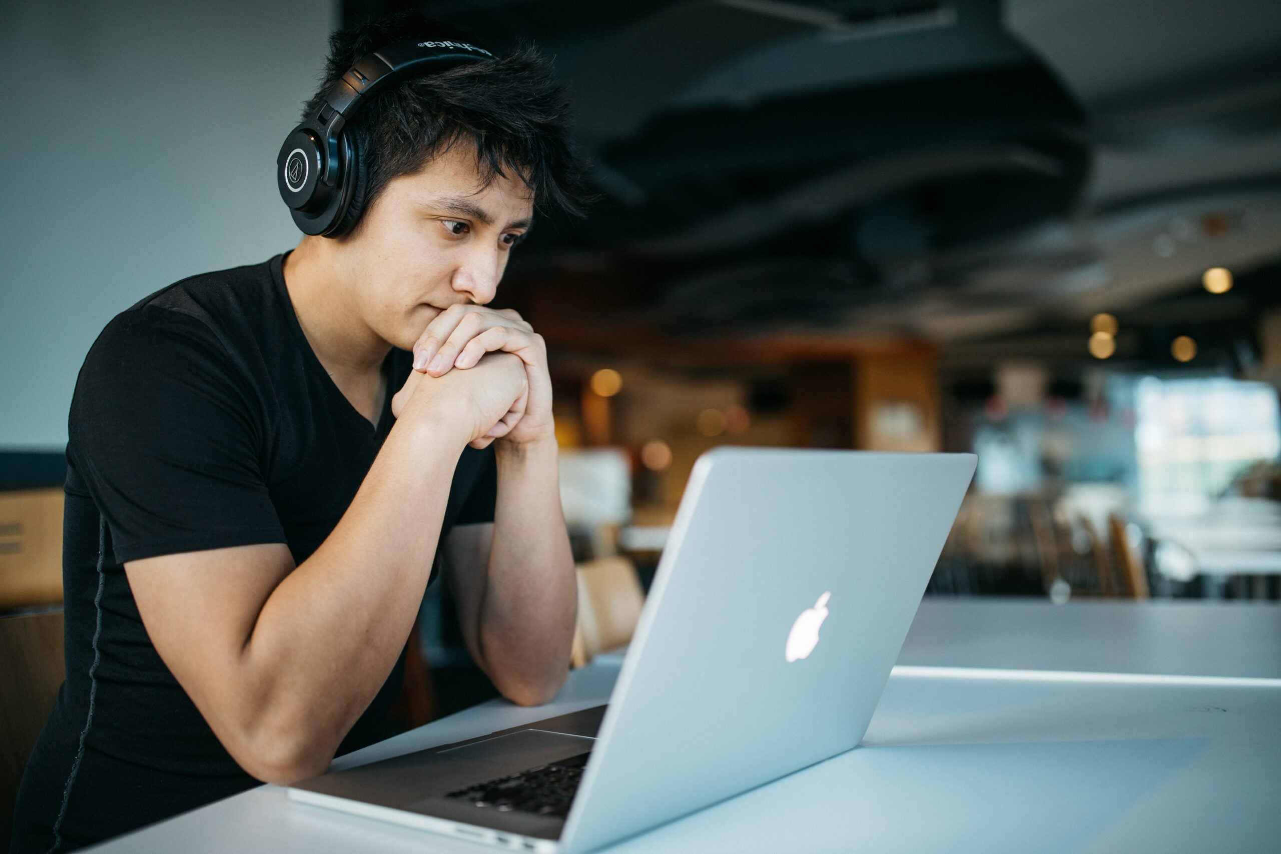 Worker sitting at Mac laptop with wireless headphones on