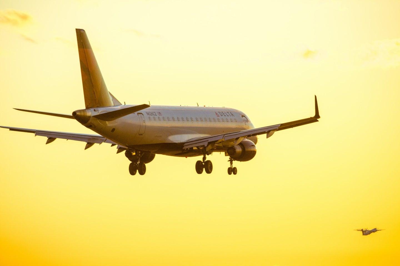 A Delta passenger plane taking off into the sun
