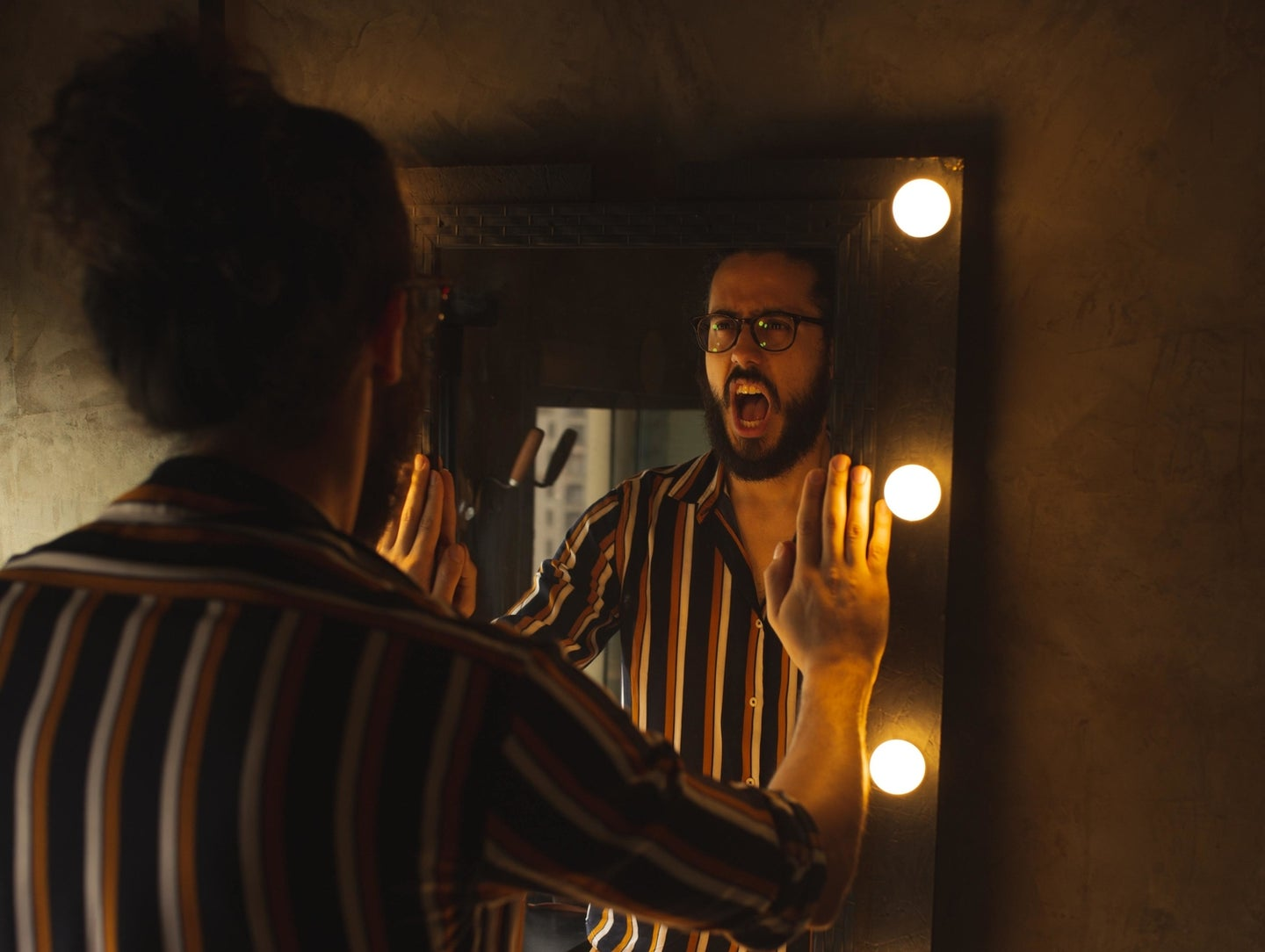 a man standing at a mirror and yelling at his reflection in the dark