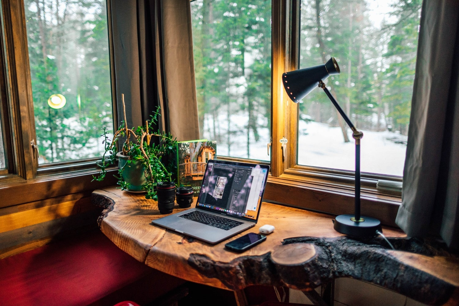 a home office with a solid wood desk and many windows looking out onto a snow-covered forest