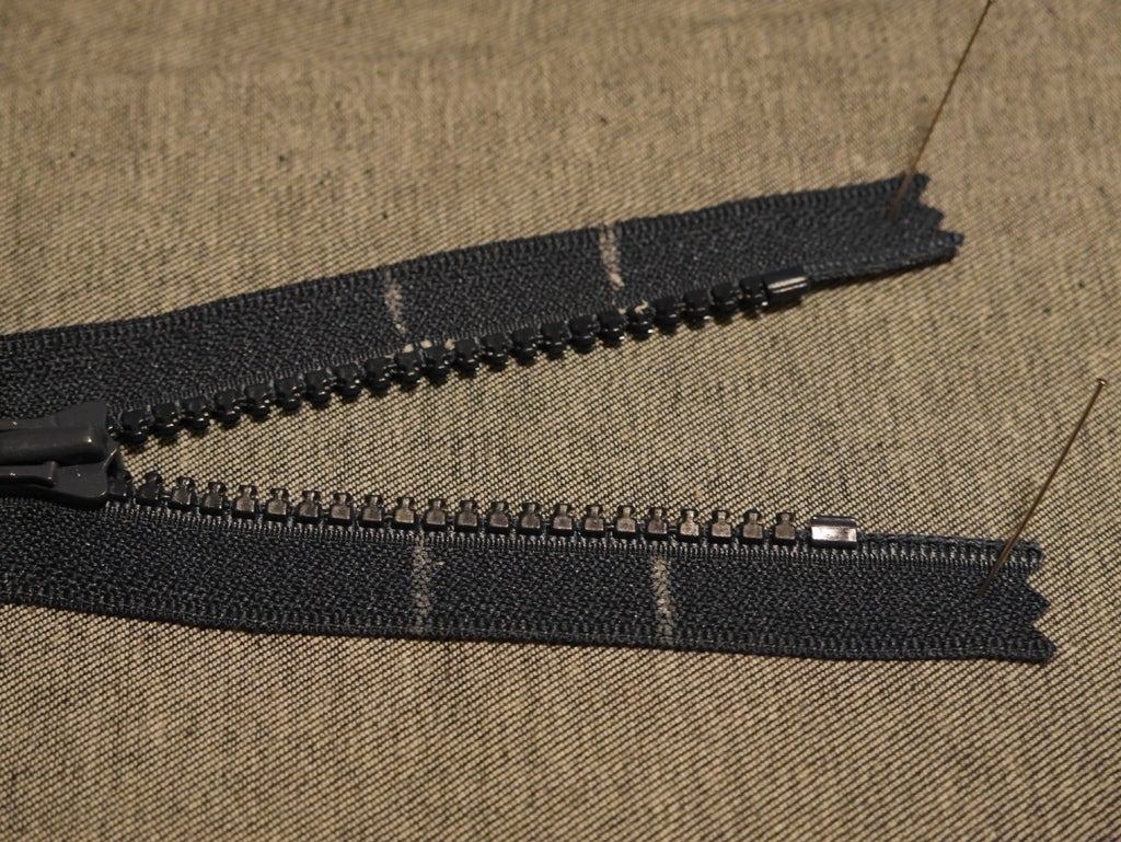 a black zipper with tailor's wax marking inches for shortening